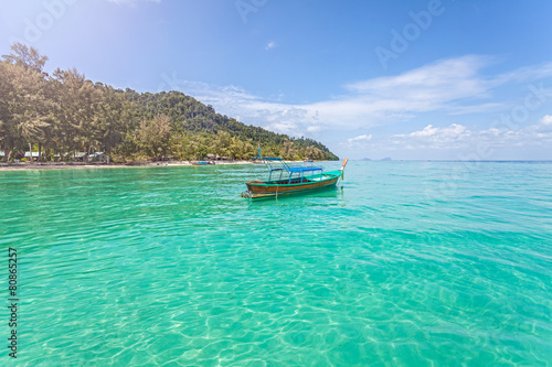 Wall Murals Green coral Little boat by tropical island, perfect vacation concept.