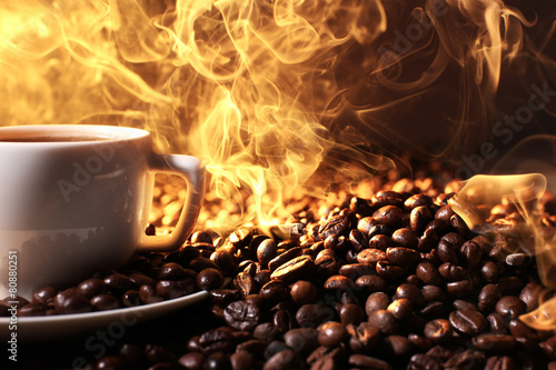 Pile of coffee beans and cup of hot coffee in beam