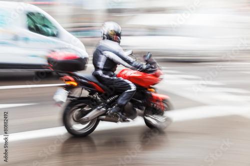 Motorrad auf nasser Straße in Bewegungsunschärfe