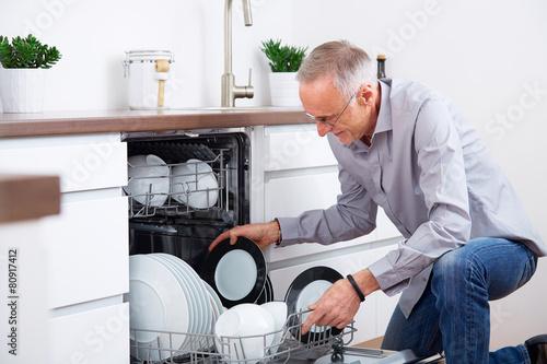 Fotografie, Obraz  Senior man in kitchen, empty out the dishwasher 7