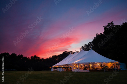 Fotomural An event tent at night with a sunset during a wedding