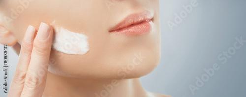 Photo  Woman applying facial cream