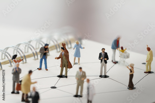 Fotografie, Obraz  close up of miniature people with social network diagram on open