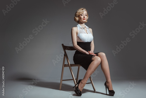 Fotografía  Pin-up girl young and beautiful woman portrait on gray