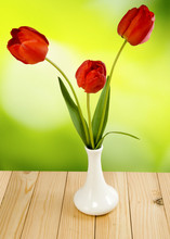 Three Flowers Tulips In A Vase On A Green  Background