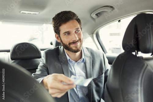 Mann, der das Taxi mit dem Bargeld zahlt Fototapete