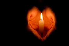 Hands Folded In The Shape Of Heart Holding A Burning Candle