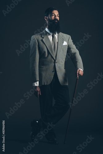 Photo  Man in Formal Suit with Cane Looking to the Right