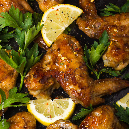 Photo  Roasted chicken wings with parsley and lemon