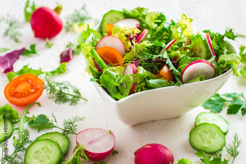 Fotografía  Healthy salad with fresh vegetables and ingredients on white bac