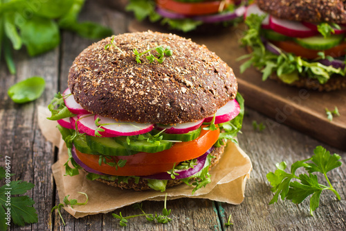Fototapeta Healthy fast food. Vegan rye burger with fresh vegetables obraz