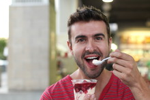 Male Eatiing A Frozen Strawberry Yogurt With With Fresh Fruits