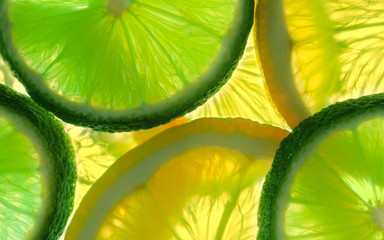 Fototapeta Owoce Lemon and green lime overlapped slices close-up background.