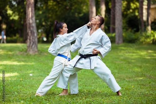 Staande foto Vechtsport Two young people practicing martial arts outdoors