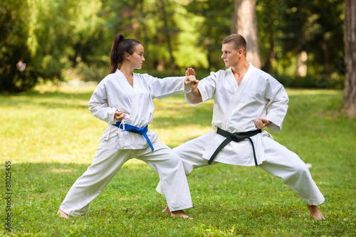 Two martial arts fighters practicing in nature