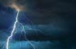 Leinwandbild Motiv Fork lightning striking down during summer storm