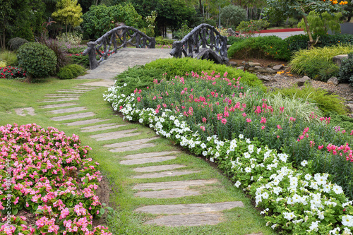 Poster Tuin landscape of floral gardening with pathway and bridge in garden
