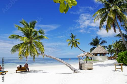 Fotografia  Tourists take sunbath on tropical beach on Maldives island
