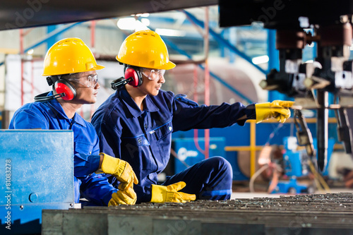 Fotografia  Worker in factory at industrial metal cutting machine