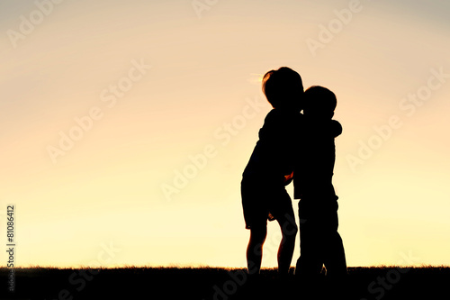 Valokuva  Silhouette of Two Young Children Hugging at Sunset