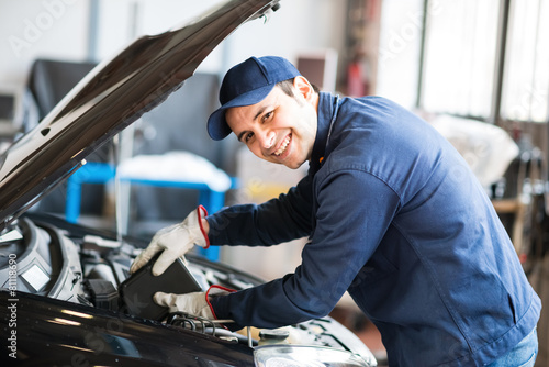 Auto mechanic putting oil in a car engine