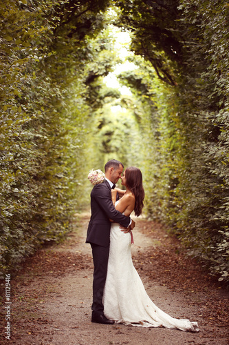 Vertical photograph of a bride and groom embracing Fotobehang
