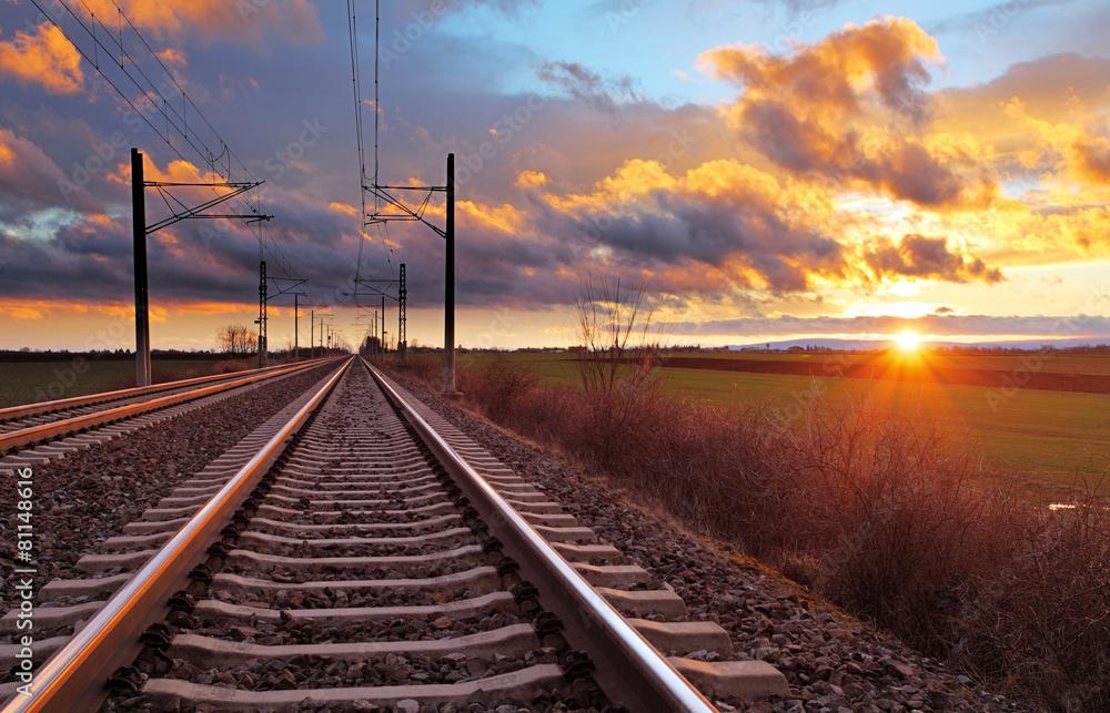 Fotografía Puesta del sol anaranjada en nubes bajas sobre ferrocarril