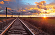 canvas print picture - Orange sunset in low clouds over railroad