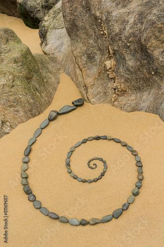 Tuinposter Vintage Poster Esoterische Spirale aus Kieseln auf Sand mit Felsen