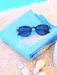 lunettes de soleil,surserviette,et sable