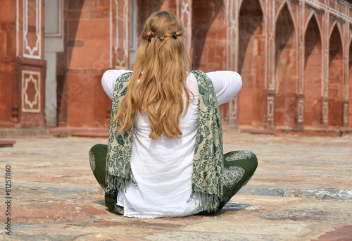 Foto  Young woman meditating in the yard of Humayun's Tomb. Delhi, Ind