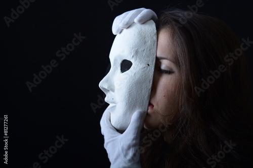 Fotografía  Chica morena la celebración de una máscara teatral de blanco