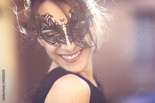 Happy Young Woman with Black Masquerade Mask