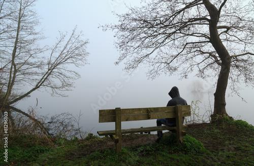 Depressed man sitting on a bench at a lake.