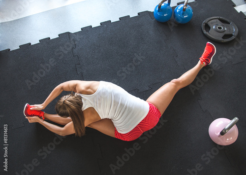 Woman worming up and stretching her body at the gym Canvas Print