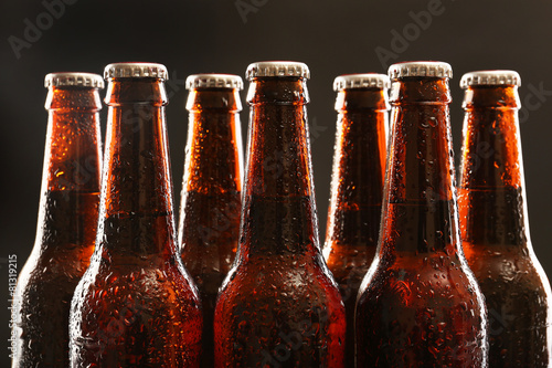 Fényképezés  Glass bottles of beer on dark background