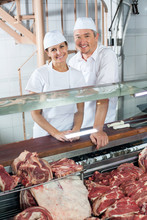 Butchers Standing At Meat Coun...