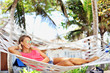 Woman in the hammock under the palms on the tropical beach