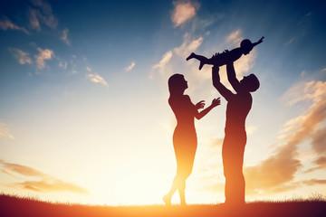 Szczęśliwa rodzina razem, rodzice z ich małym dzieckiem o zachodzie słońca