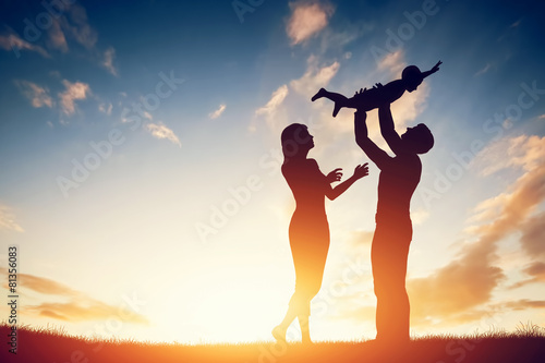 Juliste  Happy family together, parents with their little baby at sunset