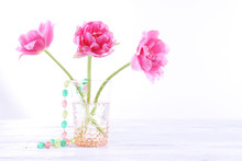 Pink Tulips In Glass Vase With Beads Isolated On White