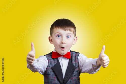 Valokuva  Excited Surprised little boy with thumb up gesture