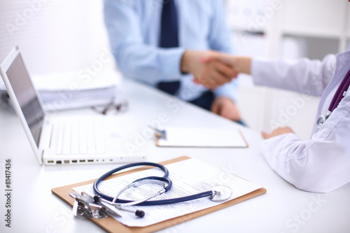 Fotografering  Doctor and Patient sitting on the desk