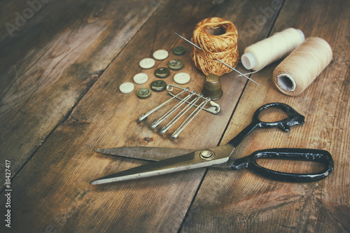 Fototapeta Vintage Background with sewing tools and sewing kit over wooden