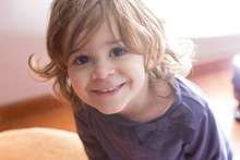 Adorable Little Girl Looking At Camera At Home