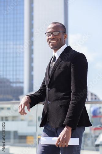 black businessman portrait on skyscrapers background Canvas Print