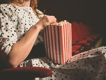 Young Woman Eating Popcorn In ...