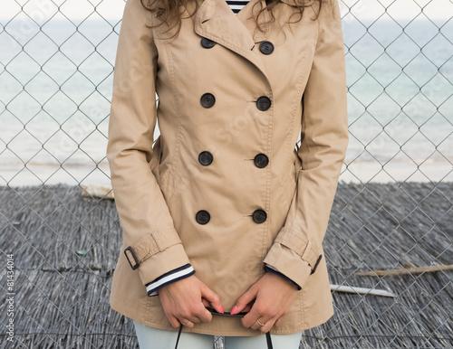 Fotografie, Tablou  Girl in a beige coat on the coast
