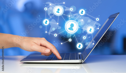 Fotografie, Obraz  Close up of hand with laptop and social media icons