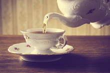 Old-fashioned Pouring Tea To Cup On Old Wallpaper Background